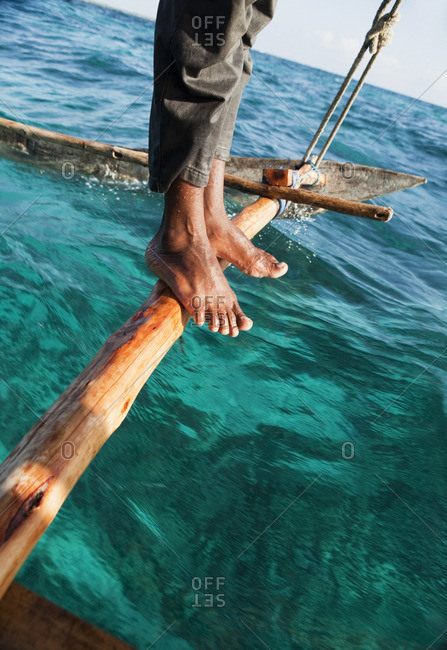 Low section of man standing on boat outrigger
