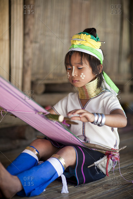 Girl in traditional dress weaving at loom