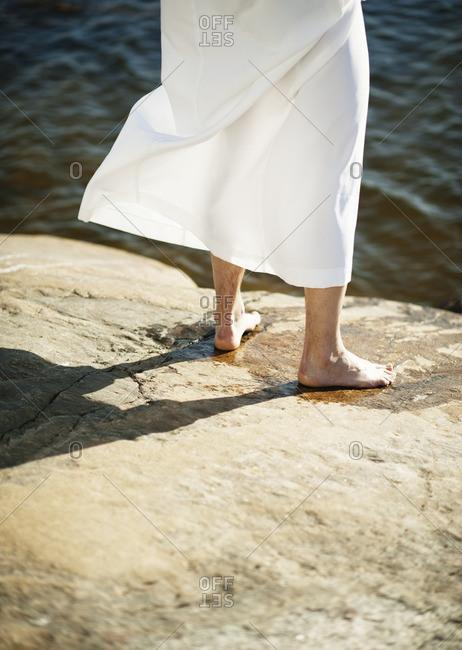Man wearing white robe standing on rock beside water