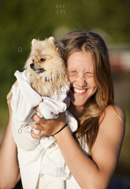 Portrait of girl holding dog wrapped in towel