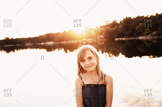 Portrait of girl by lake at sunset