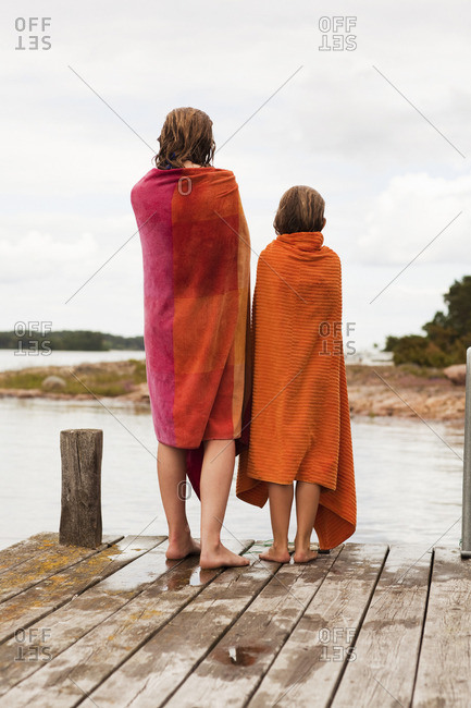 Two girls wrapped in towels standing on jetty