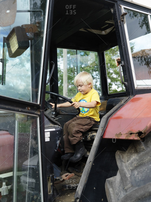 A small boy driving a tractor