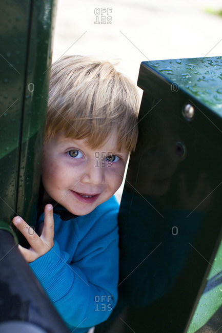 A boy peeking out of a fence