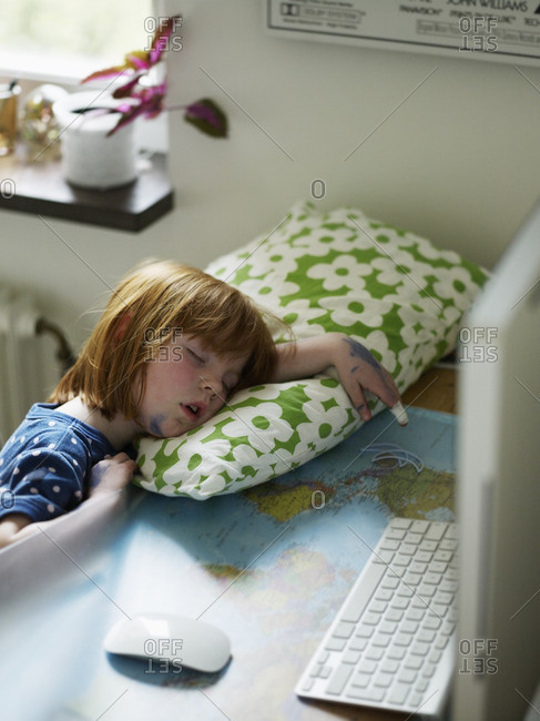 Girl sleeping on table beside computer