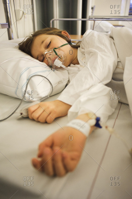 Girl lying on hospital bed with oxygen mask over face
