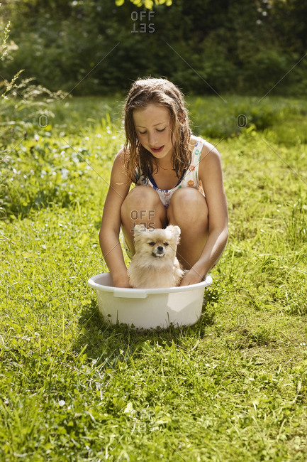 Girl giving bath to pet dog in garden