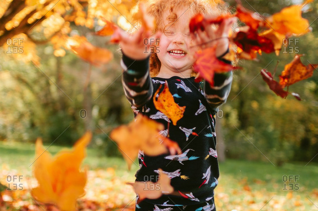Little boy in pajamas throwing leaves into the air