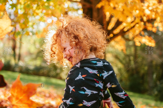 Little boy smiling and playing in autumn leaves
