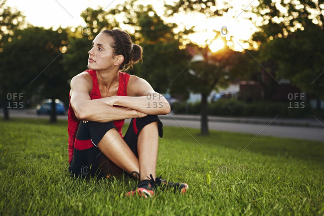 Woman in workout clothes sitting in the grass