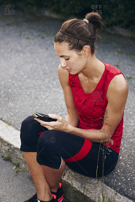 Woman in workout clothes holding mobile phone