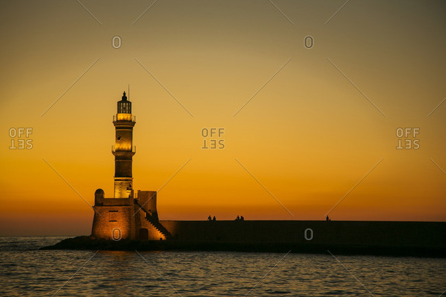 Illuminated lighthouse at sunset
