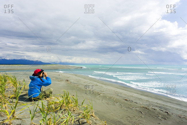 Woman Sits Edge Of Beach Near Mouth Of Alsek River Viewing Scenery Glacier Bay National Park Alaska Summer