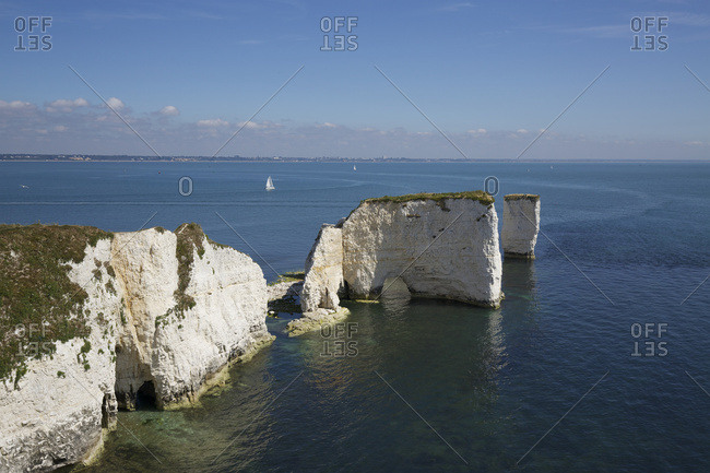 Dramatic limestone cliffs and off shore stacks with archways and caves set in calm blue sea