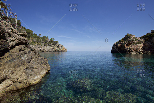 Crystal clear water and beach cafe perched on rocky promontory, Deia bay, Mallorca