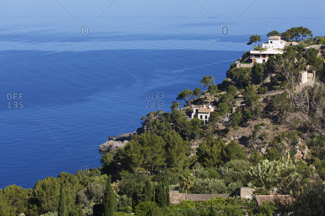 Sea view with tree covered promontory and villa from the coastal road between Soller and Pollenca, Mallorca