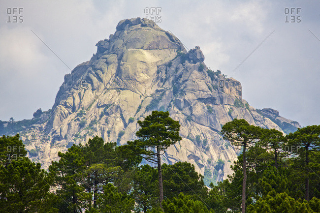 Dramatic mountain peak fringed by forest