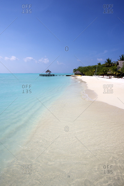 Classic white sand beach with blue sea and overwater cabana