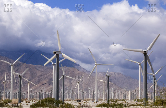 A field of wind generators with mountains and clouds in the background, a common sight in California; Palm Springs, California, United States of America
