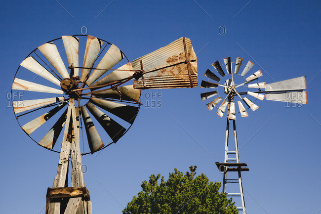 Close up view of two old windmills standing in the yard of a farm; Quemado, New Mexico, United States of America