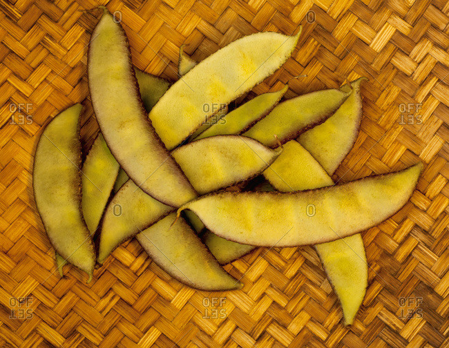 A handful of a tropical variety of peapods from a local farmers market rest on a woven mat on the Big Island; Pahoa, Island of Hawaii, Hawaii, United States of America