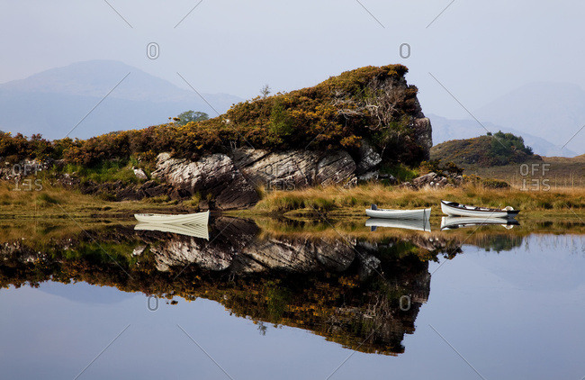 Canoes moored along the shoreline with a mirror image of a rugged cliff reflected in the water in Killarney National Park; County Kerry, Ireland