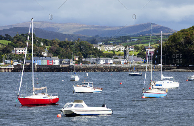 Boats moored in the harbor with storm clouds and mountains in the distance; Bantry, County Cork, Ireland