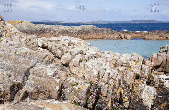 Rugged rock along the coast with an aqua water lagoon and mountains in the distance; Connemara, County Galway, Ireland