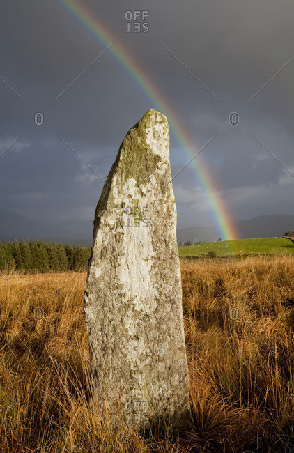 A rainbow over the storm clouds with a historic stone in the foreground in a field, near Sneem; County Kerry, Ireland