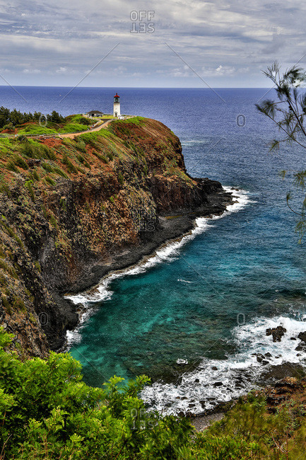 A lighthouse at the end of a trail above a cliff along the coast, Kilauea Point; Hawaii, United States of America