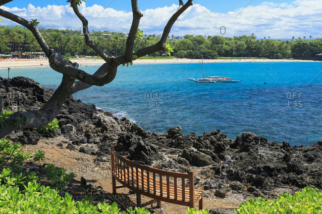 Resting bench on Kaunaoa Bay, one of the 'world's best beaches' and site of Mauna Kea Hotel; Kohala, Island of Hawaii, Hawaii, United States of America