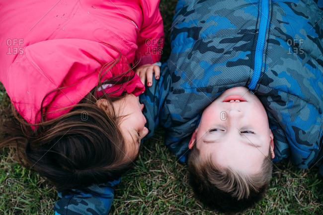 Brother and sister in jackets lying on grass together