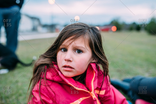 Little girl sitting on a lawn looking worried