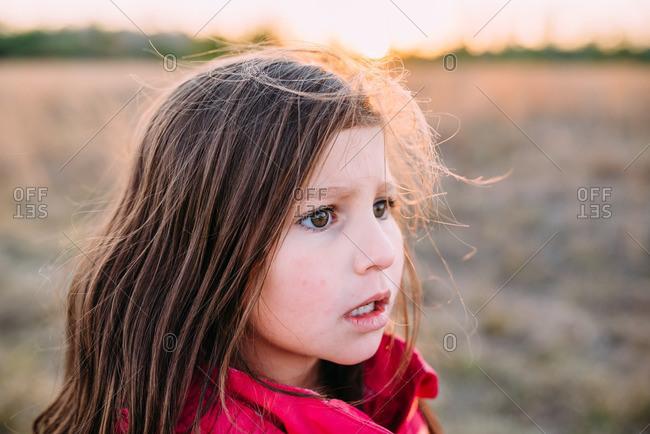 Little girl standing in a field looking worried