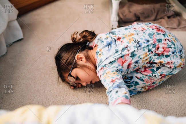 Little girl in a floral dress curled up on a carpeted floor
