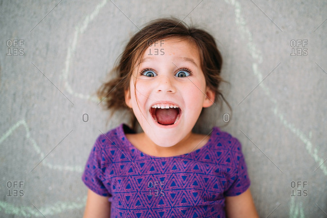 Little girl lying on a sidewalk smiling and yelling