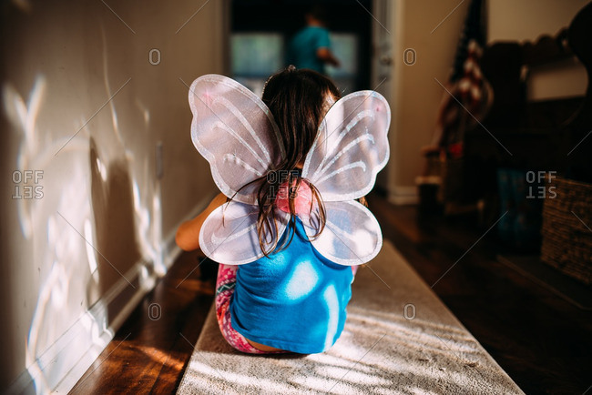 Little girl wearing sparkly butterfly wings sitting in a hallway