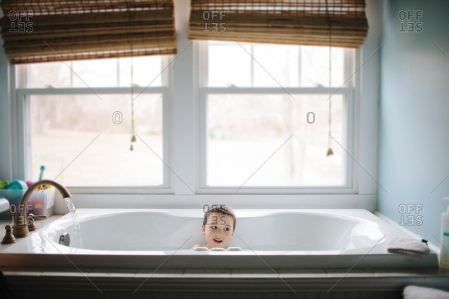 Boy sitting in tub during daytime