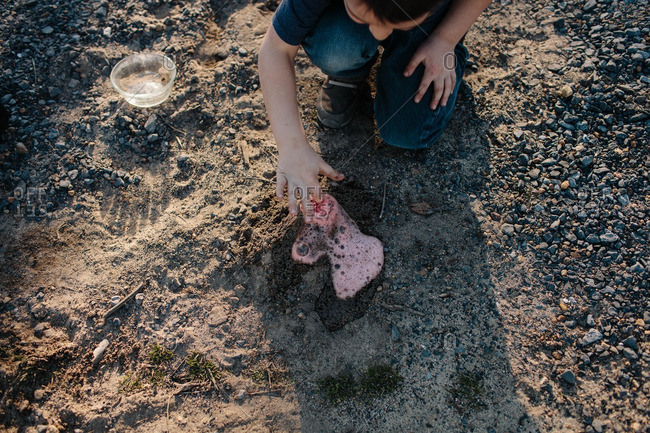 Boy making volcano in the dirt