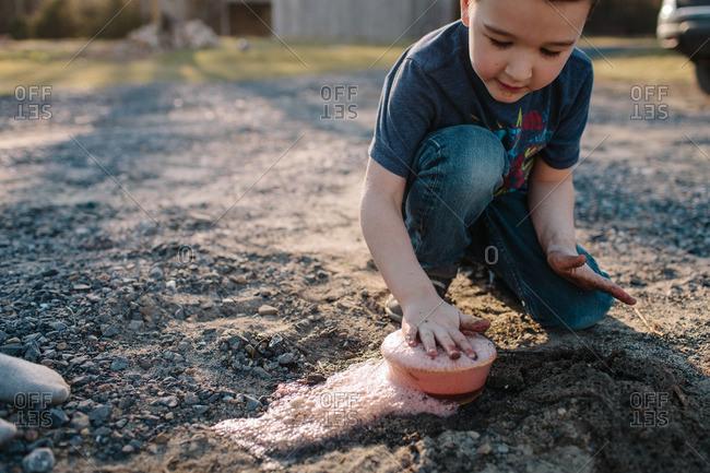 Boy making foam in bowl outside