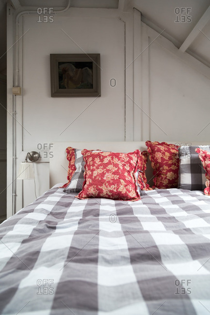 A cozy bed with checkered comforter