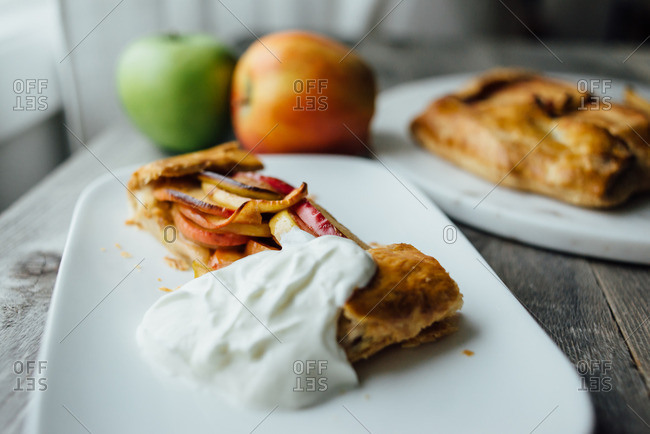 Close up of a slice of apple galette with whipped cream