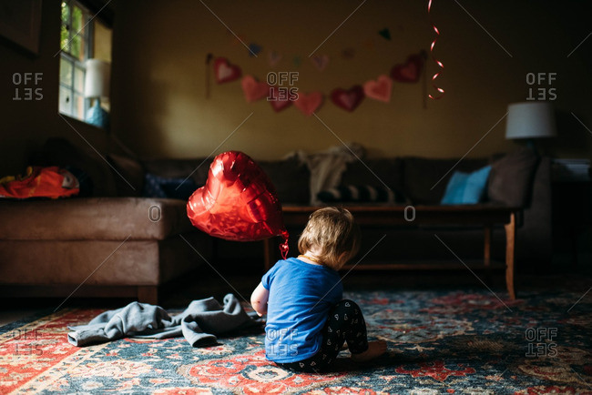 Toddler girl playing with a red heart balloon at home.