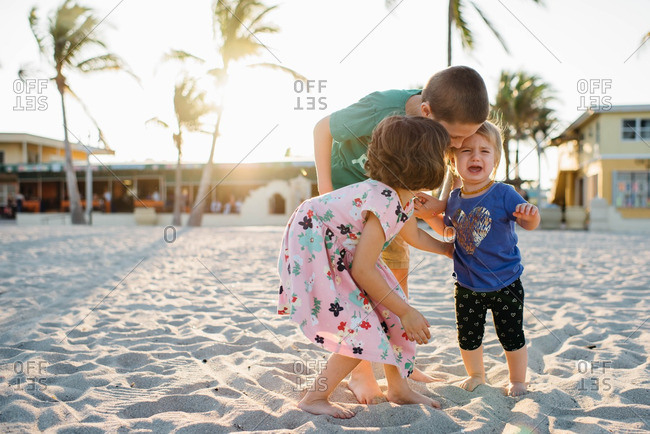Brother and sister comfort their toddler sister on the beach while she is upset.