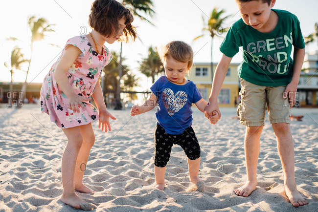 Older brother and sister hold hands of toddler girl as she walks on the sand on the beach.