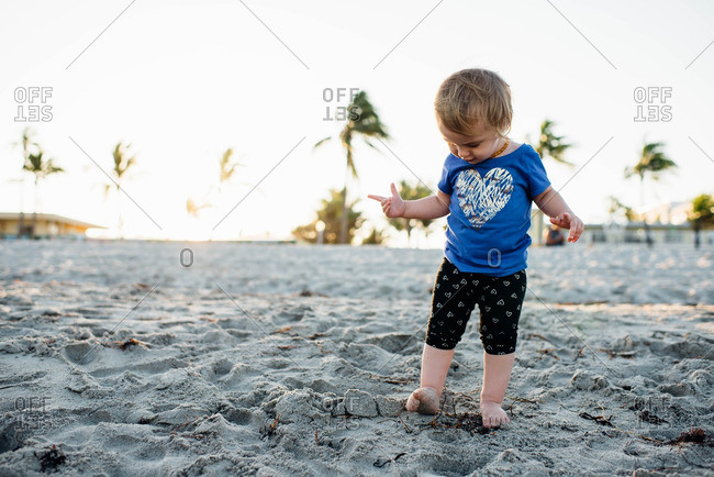 Toddler girl standing in the sand on the beach with her toes feeling the sand.