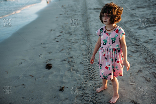 Young girl with bangs standing near the water's edge at sunset.