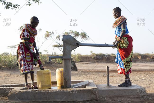 Samburu tribal women collecting fresh water from well in desert landscape, Kenya, Africa