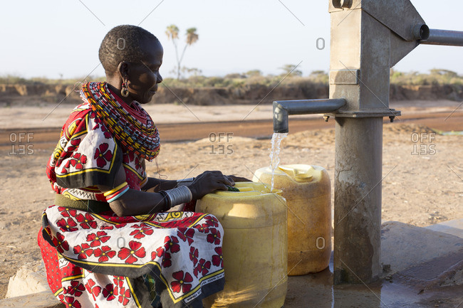 Samburu tribal woman collecting jugs of fresh water from a well in Kenya, Africa