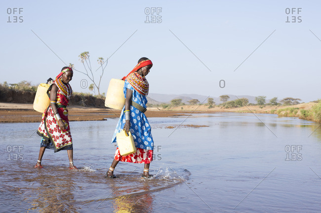 Two women from Samburu tribe carrying containers of water across river